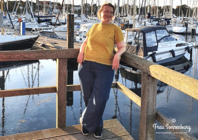 Frau in gelbem Shirt im Abendlicht am Segelhafen Boote im Hintergrund
